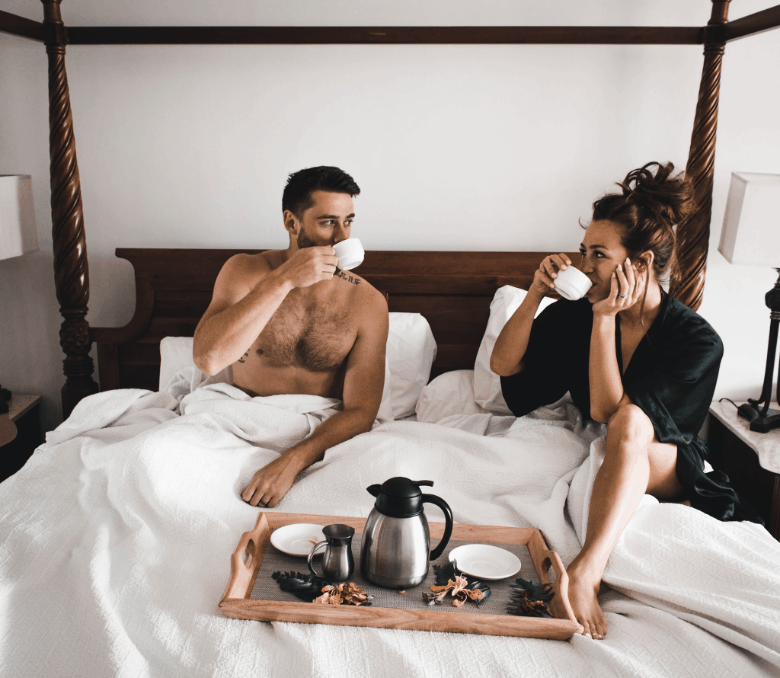 man and woman in bed drinking coffee eating breakfast